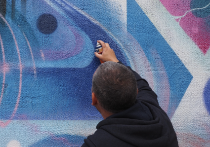 MR.CENZ painting a wall outside his studio