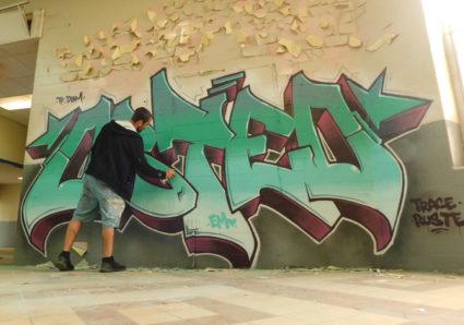 Abandoned prison interior decorating with graffiti artist OSTEO